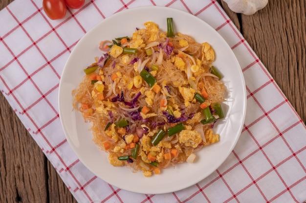 Mescolare le tagliatelle di vetro fritte con le uova e metterle su un piatto su un panno bianco rosso.