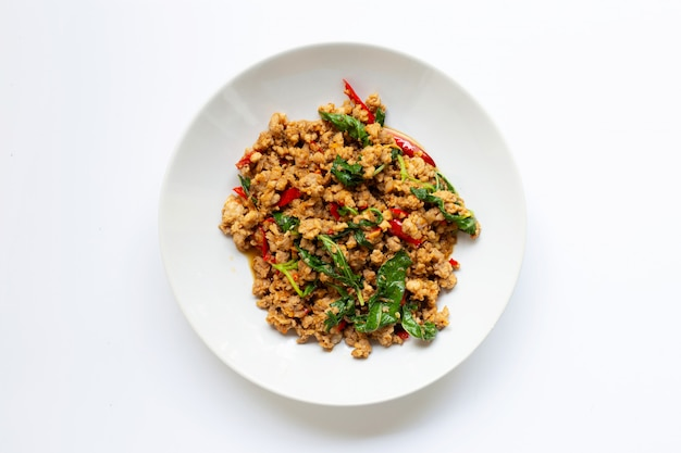 Stir-fried hot and spicy pork with basil on white.