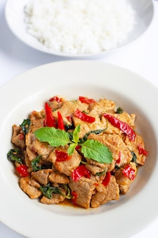 Stir-fried hot and spicy pork with holy basil on white.