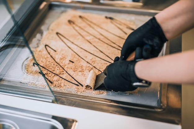 Жареные булочки с мороженым в морозильной камере. десерт из мороженого ручной работы на холодной тарелке. машина для жареного мороженого со стальной охлаждающей сковородой.