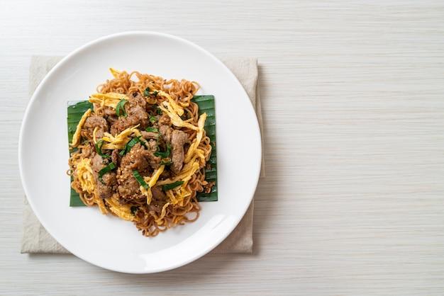 Жареная лапша быстрого приготовления со свининой и яйцом - местная азиатская уличная еда