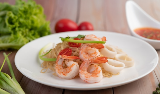Жареная лапша быстрого приготовления с креветками и крабовой палочкой в белом блюде.