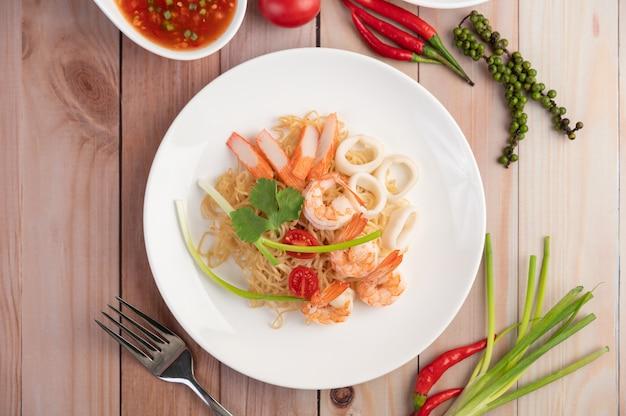 海老と蟹の棒が入ったインスタント麺を白い皿に炒めます。