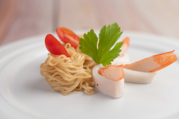 Stir-fried instant noodle with prawn and crab stick along  in a white dish.