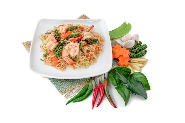 Stir-fried instant noodles with fresh shrimps and herb on white.