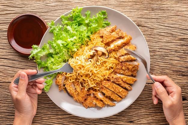 Жареная лапша быстрого приготовления с японской жареной свиной котлетой или тонкацу, салатом и грибами шиитаке рядом с соусом тонкацу, покрытым белым кунжутом на деревенском фоне текстуры древесины, вид сверху