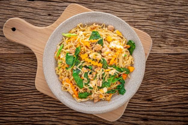 Жареную лапшу быстрого приготовления со свининой, яйцом, китайской капустой, морковью и перцем в треснувшей керамической тарелке