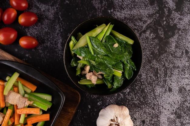 ケールと豚バラ肉を木の板にのせたプレートで炒めます。