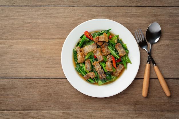나무 테이블 태국 음식 개념에 튀긴 케일, 매운 바삭한 돼지 고기를 저어.