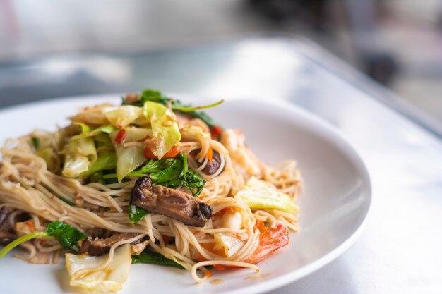 Stir-fried kee mao pasta in thai street restaurant