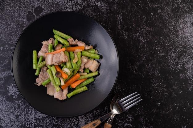 Обжарить длинную фасоль и морковь, добавить свиную грудинку, выложить на черную тарелку.