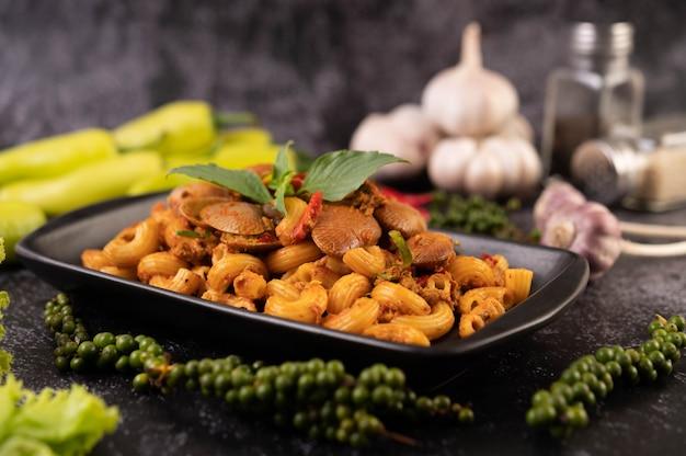 Жареные макароны с моллюсками на черной тарелке.