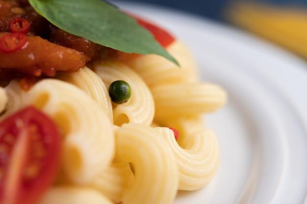 白い皿にトマト、チリ、コショウの種、バジルとマカロニを炒めたもの。
