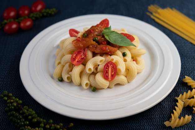 Stir-fried macaroni with tomato, chili, pepper seeds and basil in a white dish.