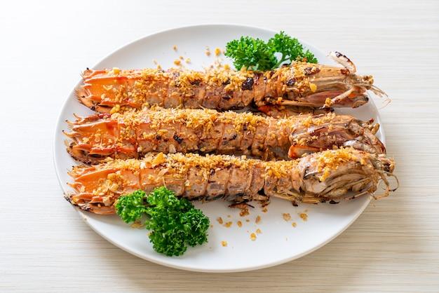 Жареные креветки богомола с чесноком на белой тарелке