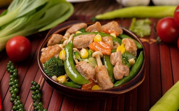 グリーンピース、にんじん、きのこ、とうもろこし、ブロッコリー、豚肉を含む混合野菜の炒め物