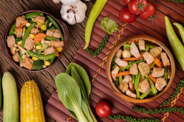 Verdure miste saltate in padella contenenti piselli, carote, funghi, mais, broccoli e maiale