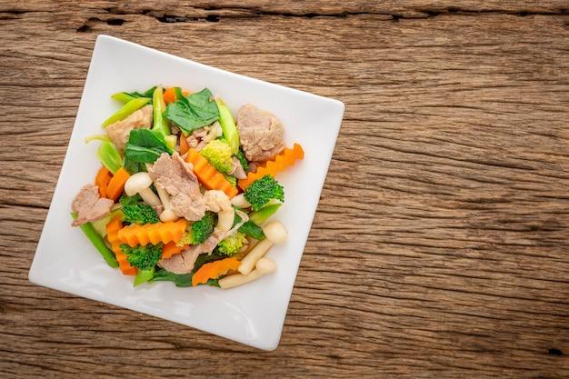 ブナシメジの豚肉としめじの炒め物を白い四角いセラミックプレートの上面図で炒めます