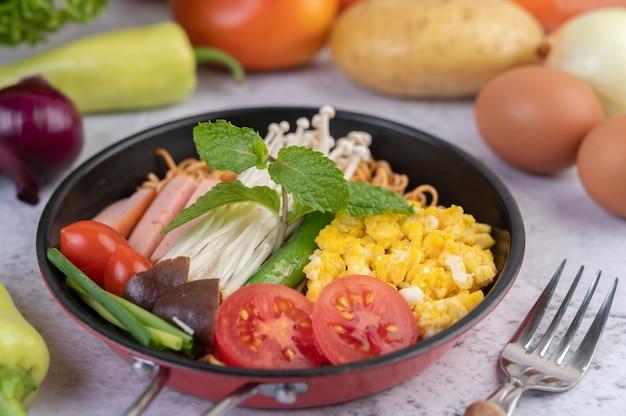Mescolare la pasta fritta che combina mais, funghi con ago d'oro, pomodoro, salsiccia, edamame e cipollotti in una padella.