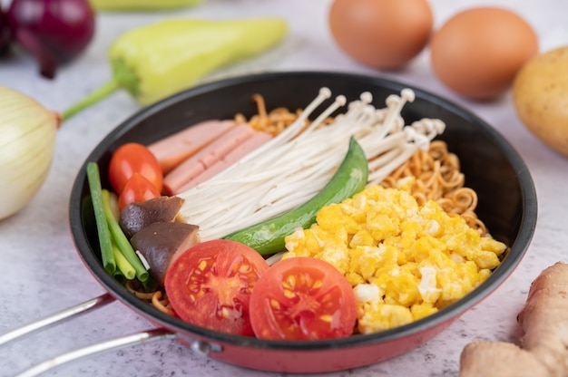 Stir fried noodle that combines corn, golden needle mushroom, tomato, sausage, edamame and spring onions in a frying pan.