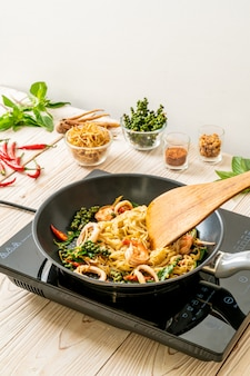 Stir fried noodle with vegetable and meat on pan