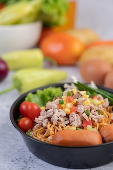 Stir-fried noodles with minced pork, edamame, tomatoes and mushrooms in a pan.