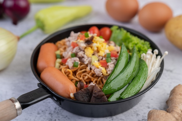 Stir-fried noodles with minced pork, edamame, tomatoes and mushrooms in a pan. Free Photo