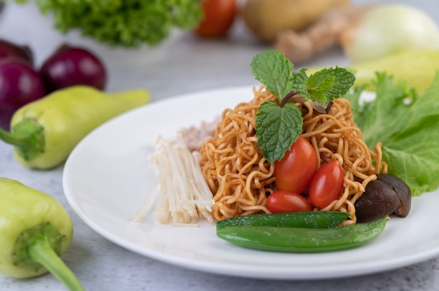 Stir-fried noodles with minced pork, edamame, tomatoes and mushrooms in a white plate.