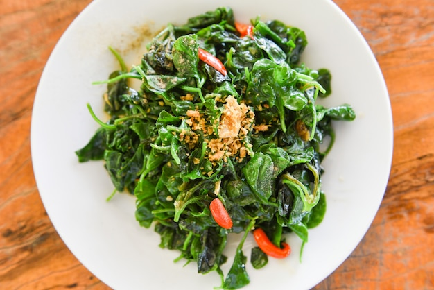 Жареный овощной кресс-салат в устричном соусе на белой тарелке