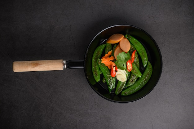 Stir-fried peas in a frying pan on black cement surface.