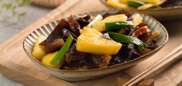 パイナップルとキクラゲの炒め物。灰色のテーブルの背景にネギと自家製のおいしい料理。