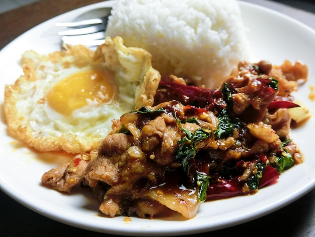 Stir-fried pork and basil and fried egg with steamed rice in a white dish