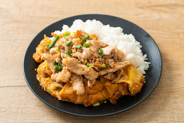 Stir-fried pork with garlic and egg topped on rice - asian food style