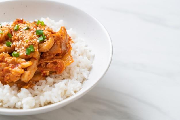 밥 위에 김치를 곁들인 돼지 고기 볶음-한국 음식 스타일