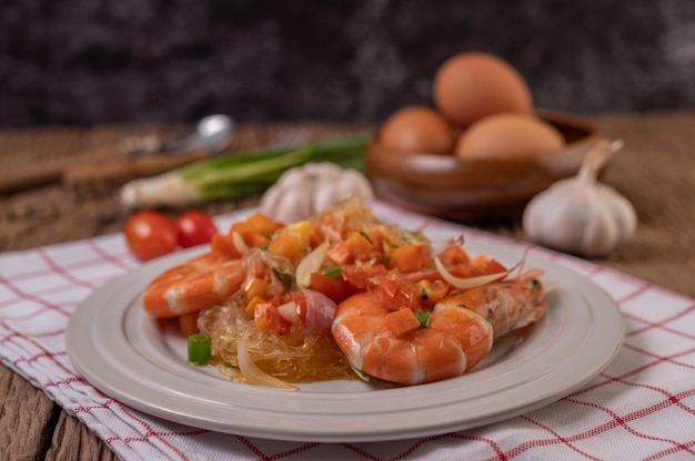 Stir-fried prawns with glass noodles in a white plate placed on a cloth with eggs and garlic.