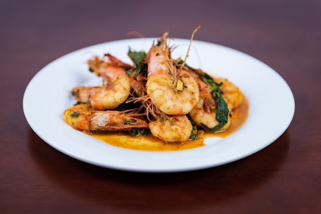Stir fried red curry with shrimp thai food on a wooden background