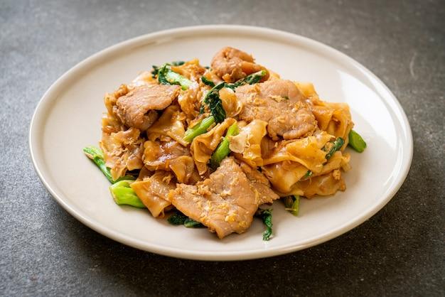Жареная рисовая лапша с черным соевым соусом, свининой и капустой