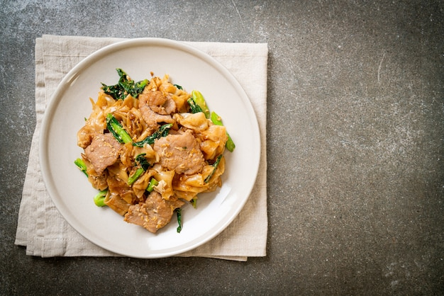 Stir-fried rice noodle with black soy sauce and pork and kale - asian food style