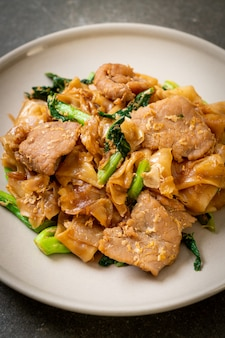 Stir-fried rice noodle with black soy sauce and pork and kale