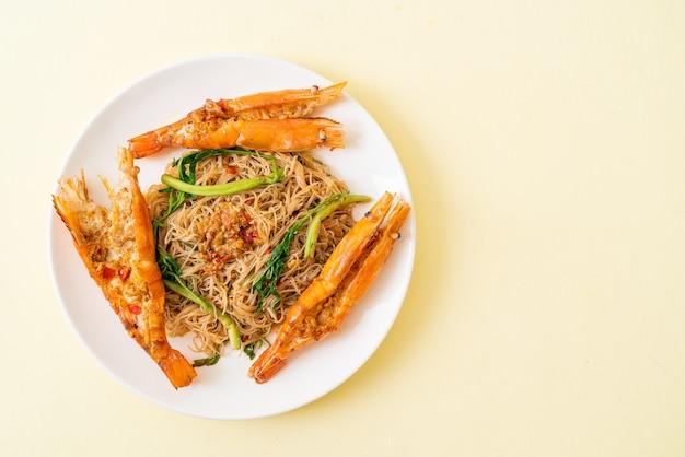 Жареная рисовая вермишель и водяная мимоза с речными креветками на тарелке