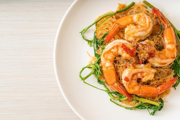 Жареная рисовая вермишель и водяная мимоза с креветками на тарелке, перемешать