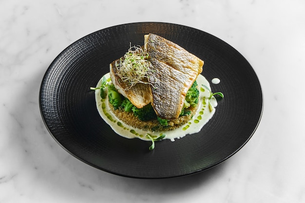 Stir-fried sea bass fillet with quinoa and broccoli garnish with creamy sauce, served in a black plate on a marble surface