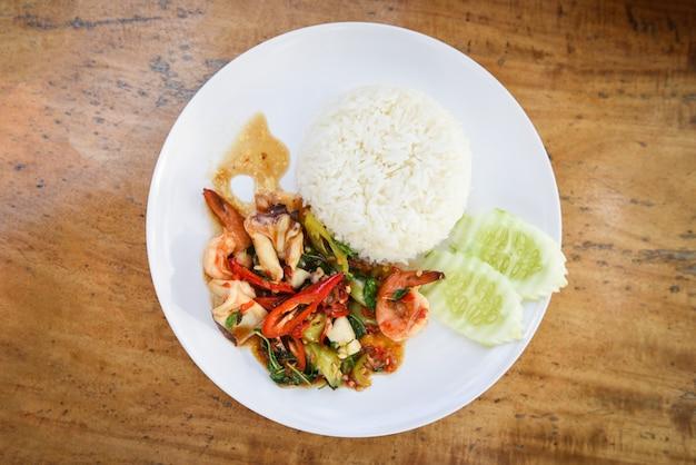 거룩한 바질과 쌀로 튀긴 해산물 오징어 새우 새우 볶음 오이와 칠리로 태국 음식 매운 튀긴 요리법