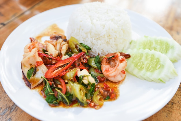 Stir fried seafood squid shrimp prawn with holy basil and rice - thai food spicy fried recipe with cucumber and chili