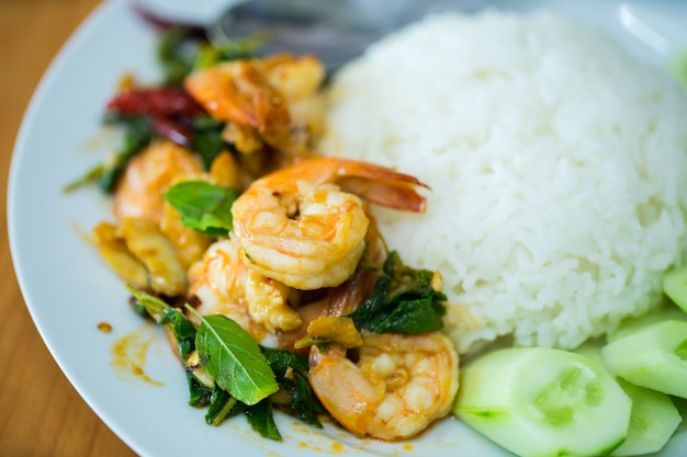 Stir fried shrimp with basil and cooked rice.