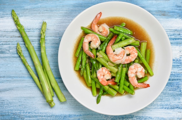 Stir fried shrimps with asparagus green on white plate and wooden table