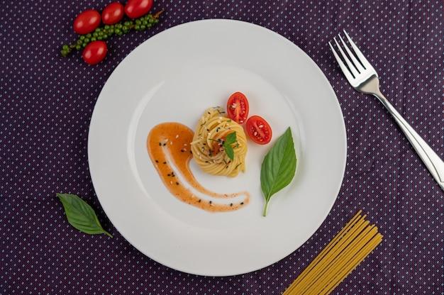 하얀 접시에 아름답게 배열 된 볶은 스파게티.