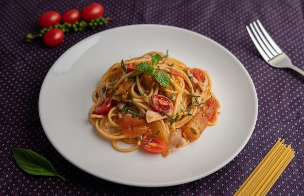 Обжаренные спагетти красиво оформлены в белой тарелке.