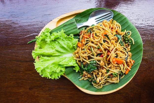 Жареные спагетти с овощами и свининой в деревянном подносе ставят на темно-коричневый деревянный стол. вид сверху.