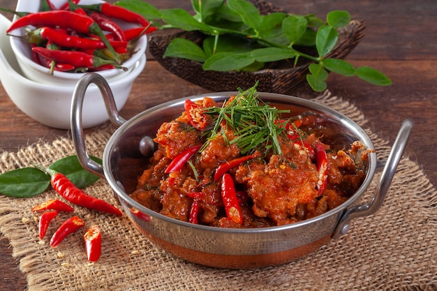 Stir fried spicy fish in a pan on a wooden